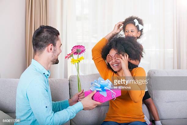 Père tenant un cadeau et des fleurs, fille couvrant les yeux des Mères