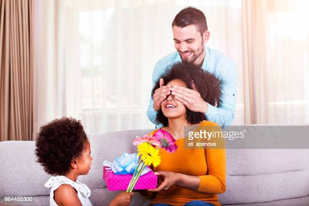 Father holding gift and flowers, daughter covering mothers eyes