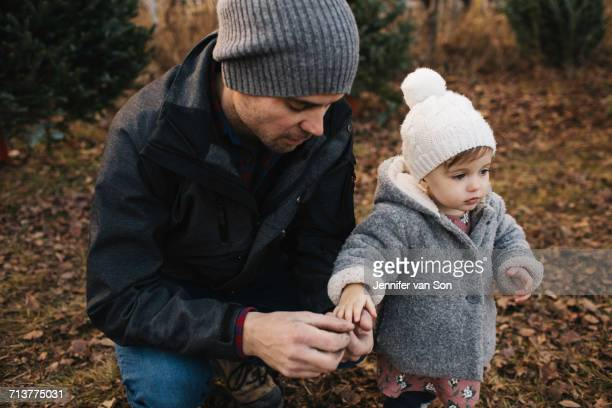 Father holding hand of baby girl in forest