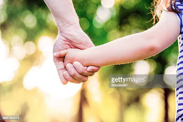Father holding hand of his little daughter