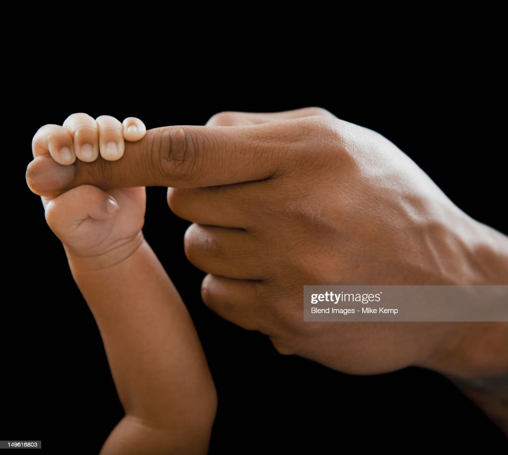 Father holding hands with newborn baby : Stock Photo