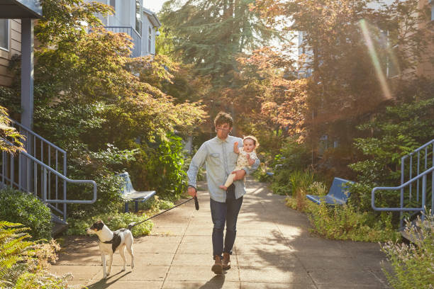 A father holding his baby and walking his dog around his neighborhood while wearing a protective face mask.