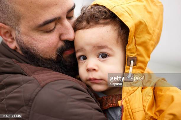 father holding his baby son with hood and looking at camera - coat stock pictures, royalty-free photos & images