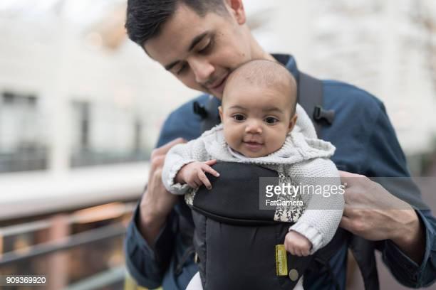 Vater mit seiner Tochter in einem Tragetuch, während in einem Einkaufszentrum
