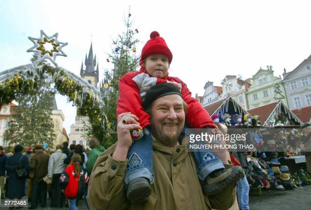 A father holding his daughter on his shoulders smiles 30 November 2003 while visiting Prague's traditional Christmas market at the Old Town Square...