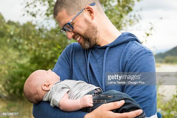 a father holding his infant son - genderblend stock pictures, royalty-free photos & images