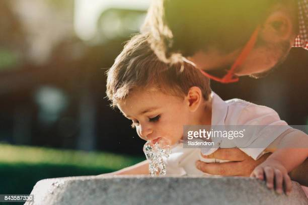 Father holding his son above a drinking water fountain