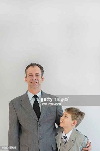 Father holding his son in his arm against white background, smiling