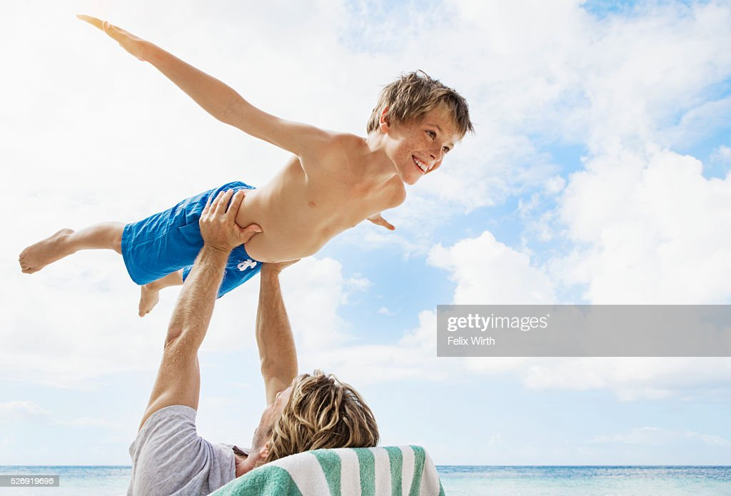 Father holding his son (10-12) mid-air while relaxing on deckchair on beach : Stock Photo