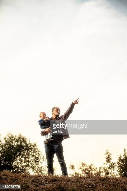 CONTENT] father holding his son standing on the hilland pointing to the sky