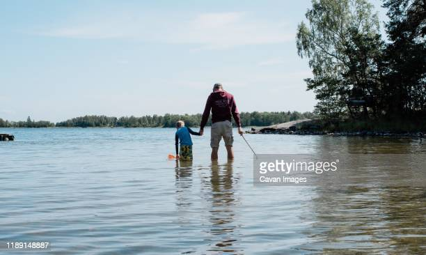father holding his son's hand whilst fishing with a net in the sea - man blue background stock pictures, royalty-free photos & images