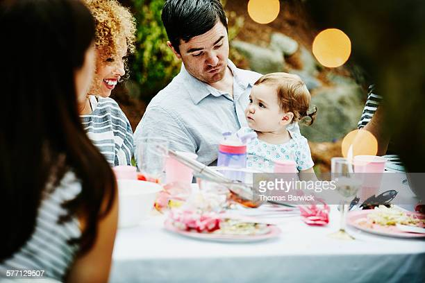 Father holding infant daughter at table