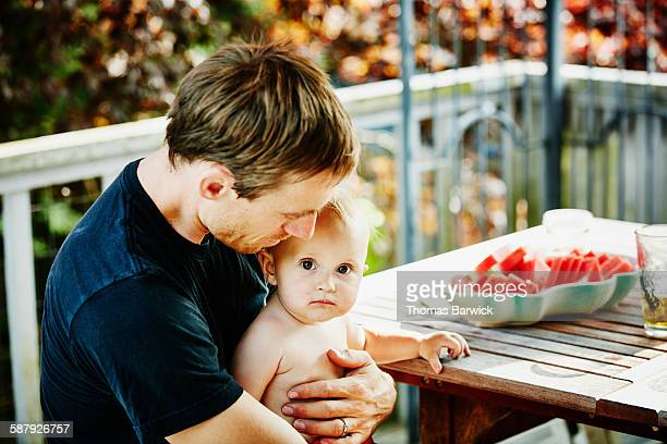 Father holding infant daughter on lap