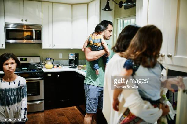 Father holding infant son while helping prepare breakfast with family in kitchen