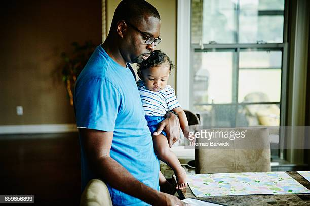Father holding infant son while setting table