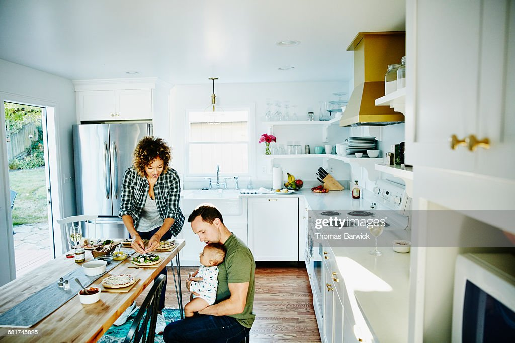 Father holding infant while preparing dinner : Stock Photo
