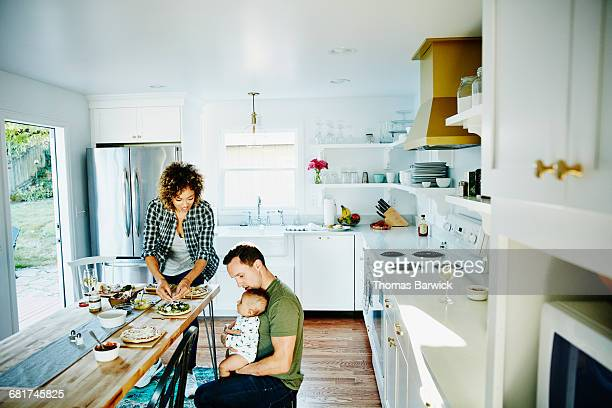 Father holding infant while preparing dinner