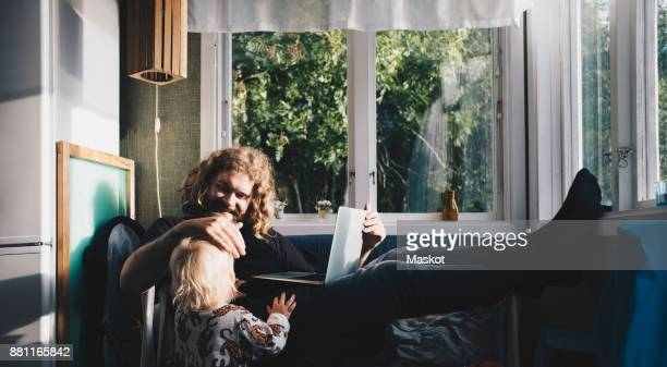 Father holding laptop while looking at girl by window