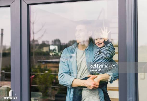 father holding laughing son, looking out of window - fenster stock-fotos und bilder