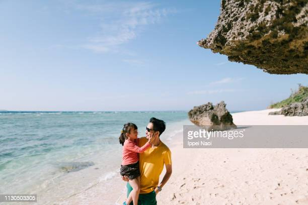 Father holding little girl and walking on tropical beach, Okinawa, Japan