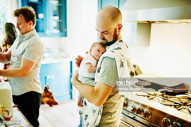 Father holding newborn baby in kitchen