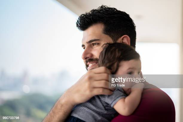 Father Holding Newborn Baby Son at Home