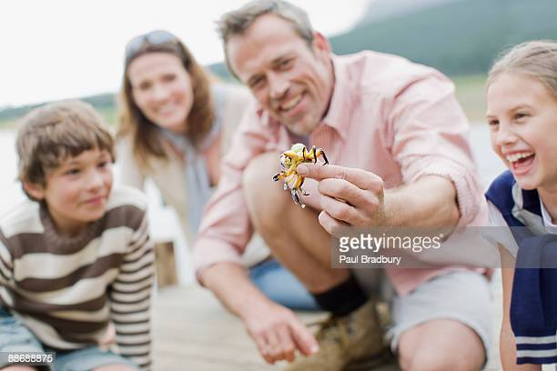 father holding out small crab - one animal stock pictures, royalty-free photos & images