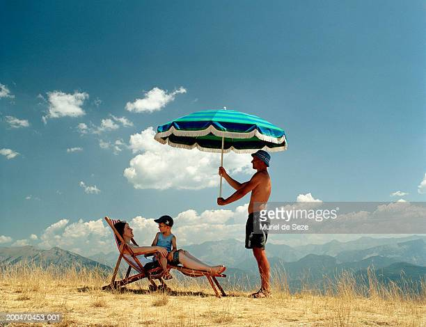 Father holding parasol over mother and son (5-7) on deckchair