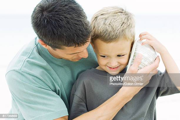 father holding seashell up to young son's ear at the beach, close-up - conch shell stock pictures, royalty-free photos & images