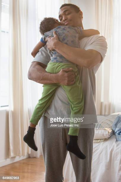 Father holding sleeping son