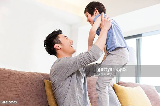 Father holding son aloft in living room