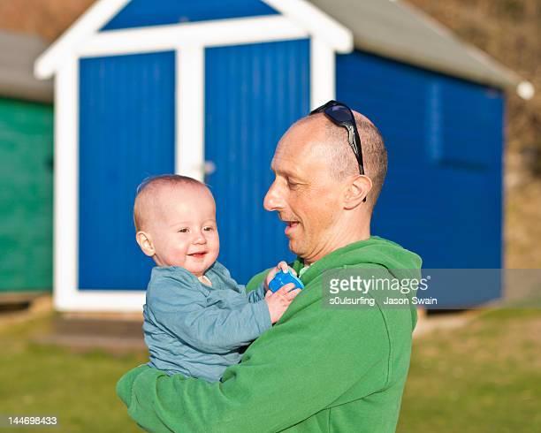 father holding son at beach - s0ulsurfing fotografías e imágenes de stock