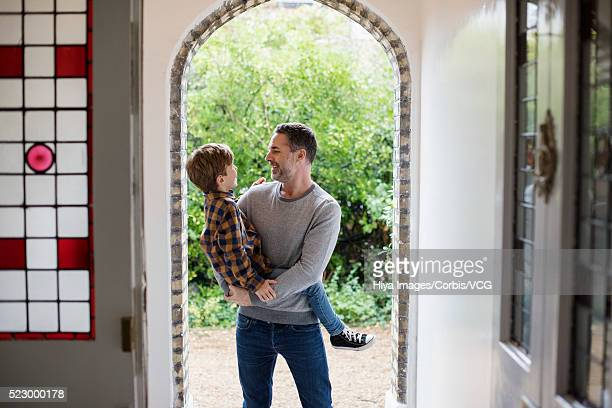 father holding son in a doorway - vcg stock pictures, royalty-free photos & images