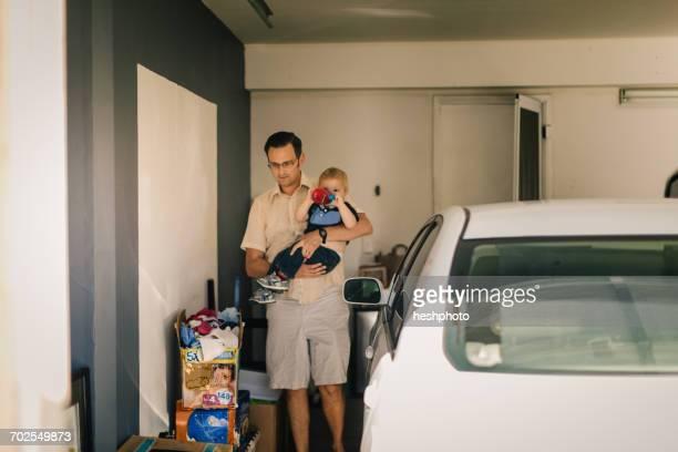 father holding son in garage - heshphoto stock-fotos und bilder