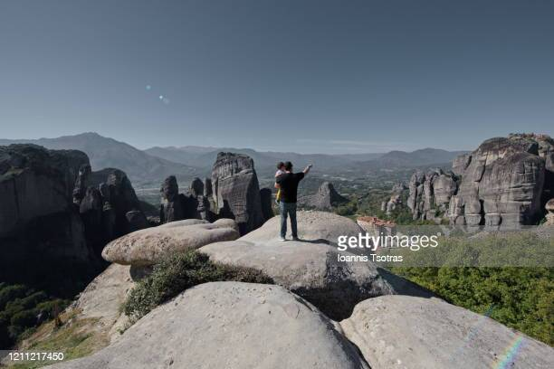 father holding son on the summit of a peak watching the astonishing view of meteora area in greece - thessaly stock pictures, royalty-free photos & images