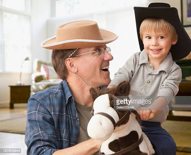 Father holding son on toy horse
