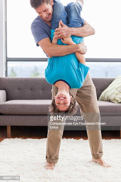 father holding son upside-down in living room - op z'n kop stockfoto's en -beelden