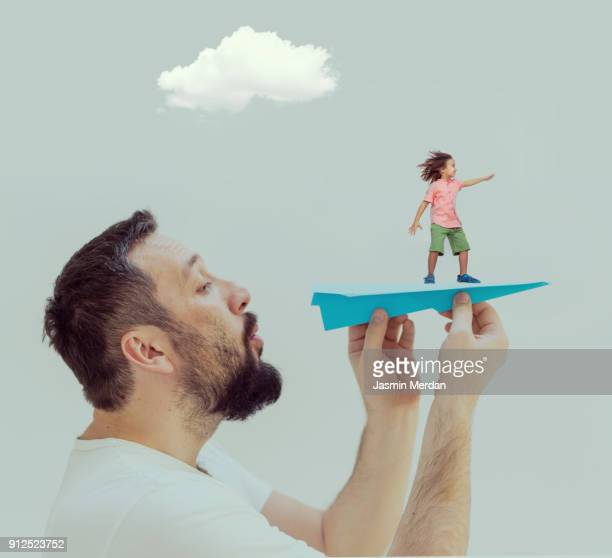 Father holding superhero son flying on paper airplane at home