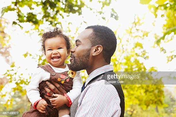Father holding toddler daughter in park