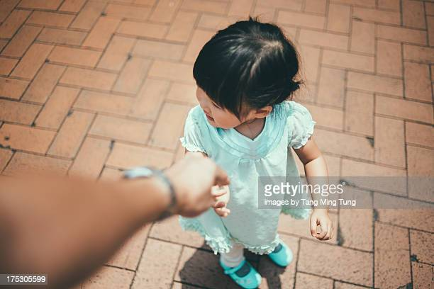 Father holding toddler girl's hand on the street