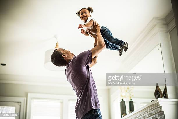 Father holding toddler in the air