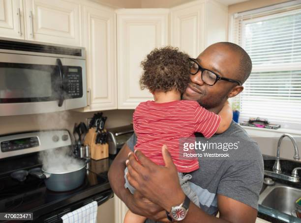 Father holding toddler son in kitchen