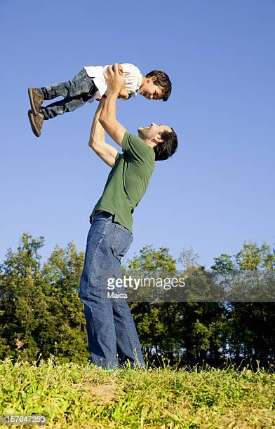 Father holding toddler son up high