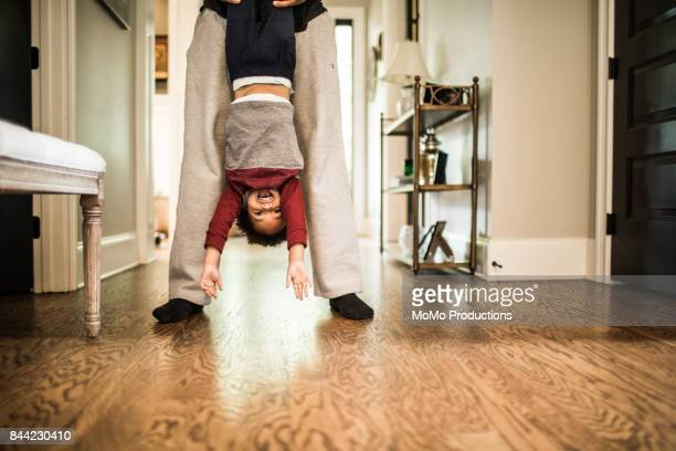 Father holding toddler son upside down