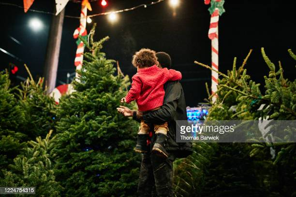 father holding toddler son while shopping for christmas tree - christmas tree stock pictures, royalty-free photos & images