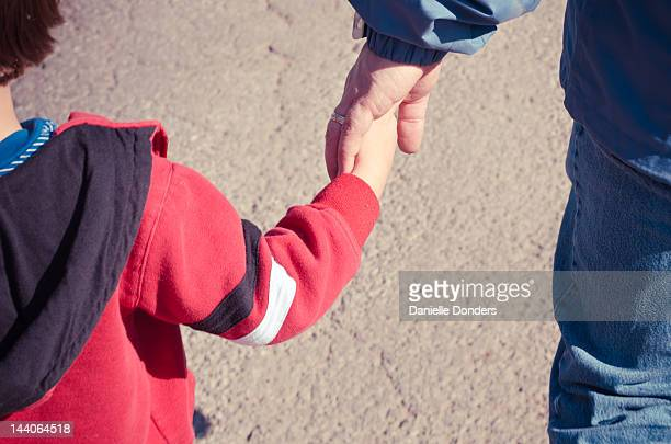 Father holding toddler son's hand