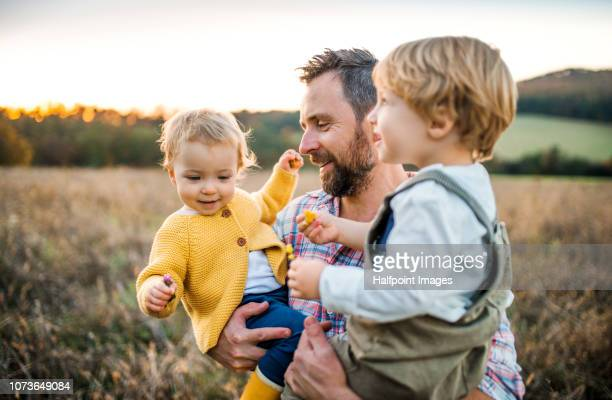 a father holding two toddler children on a meadow outdoors in autumn. - family with two children stock pictures, royalty-free photos & images