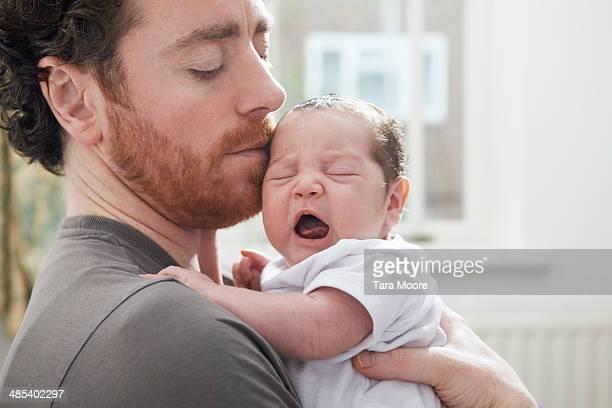 father holding yawning baby