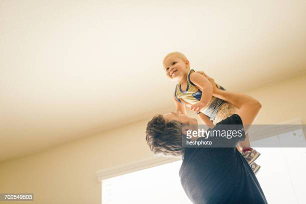 father holding young son in air, low angle view - heshphoto fotografías e imágenes de stock