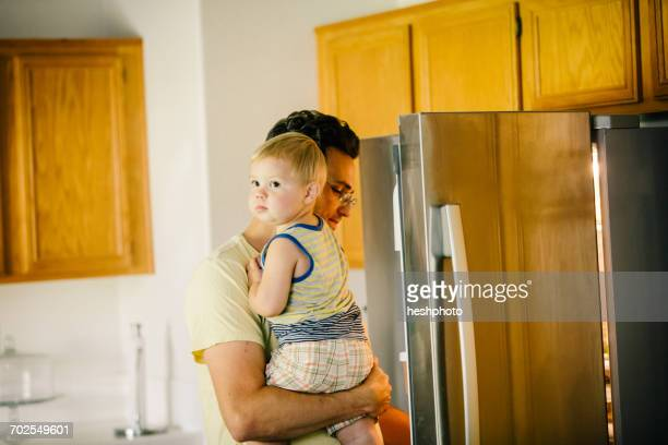 father holding young son, looking in fridge - heshphoto stock pictures, royalty-free photos & images